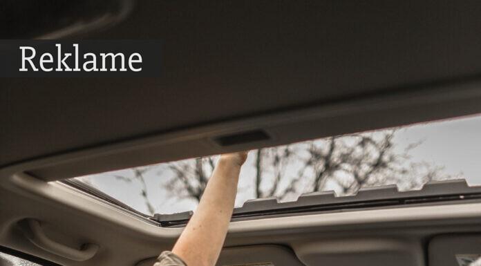 Kvinde rækker hånden ud af soltaget på sin bil